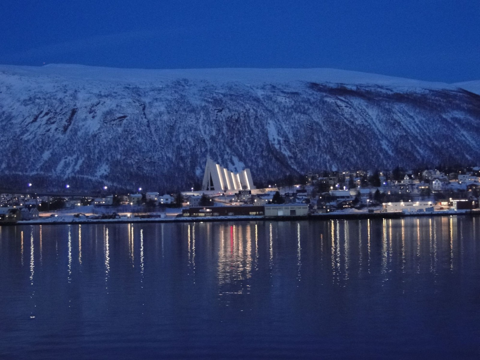 The Artic Cathedral at Tromso. Late afternoon before sailing north, the daylight had faded quickly leaving a beautiful blue glow with the lights of the cathedral providing lovely reflections on the water.