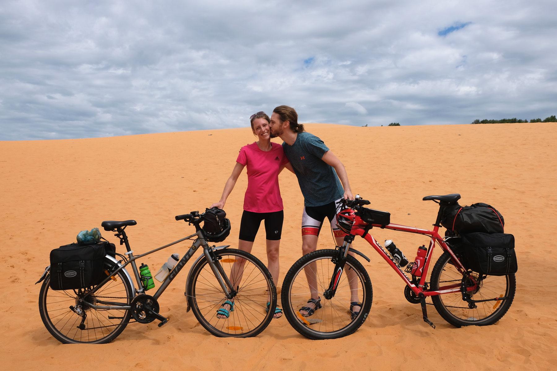 Sebastian und Leo stehen mit ihren Fahrrädern auf einer Sanddüne.